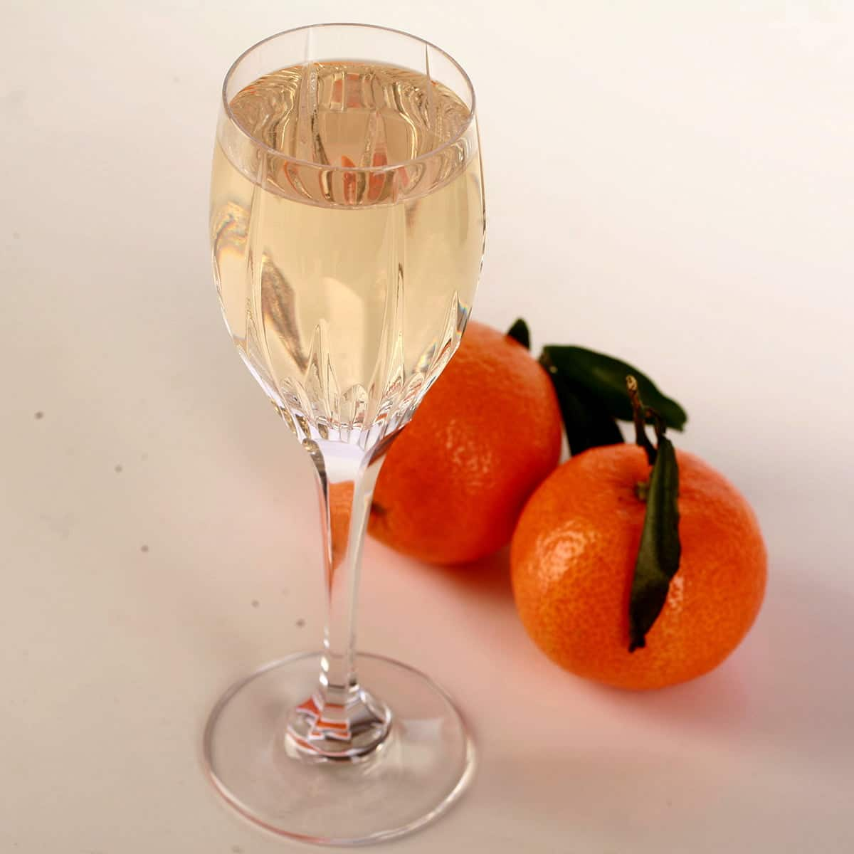 A glass of clementine mead is pictured with two clemetines at the base.