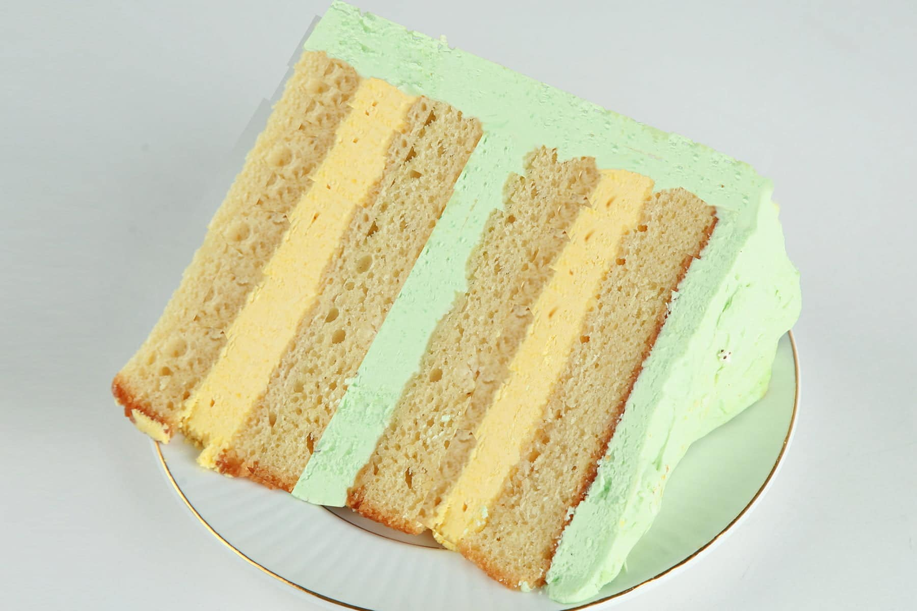 A slice of mango mojito torte. 4 layers of a mango rum cake, separated by layers of mango and mint buttercream.