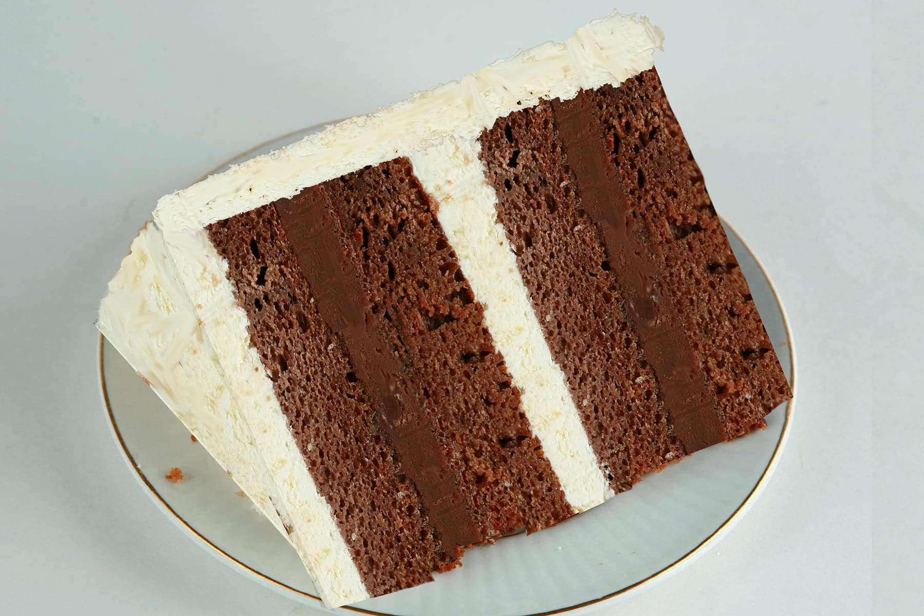 A slice of milk chocolate cardamom pear cake. 4 layers of milk chocolate cake, separated by layers of cardamom ganache and pear buttercream.