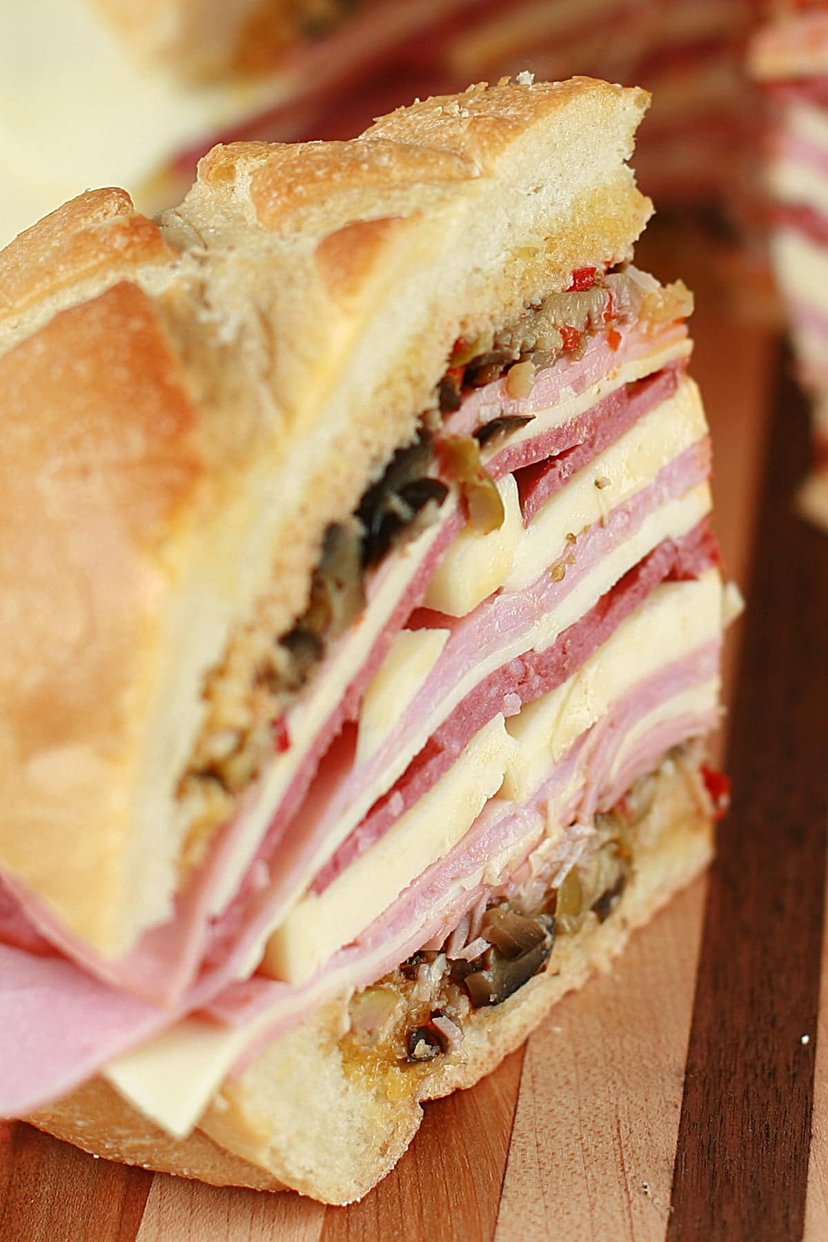 A large muffaletta sandwich: A full loaf of bread, stuffed with many layers of meats, cheeses, and olive salad.