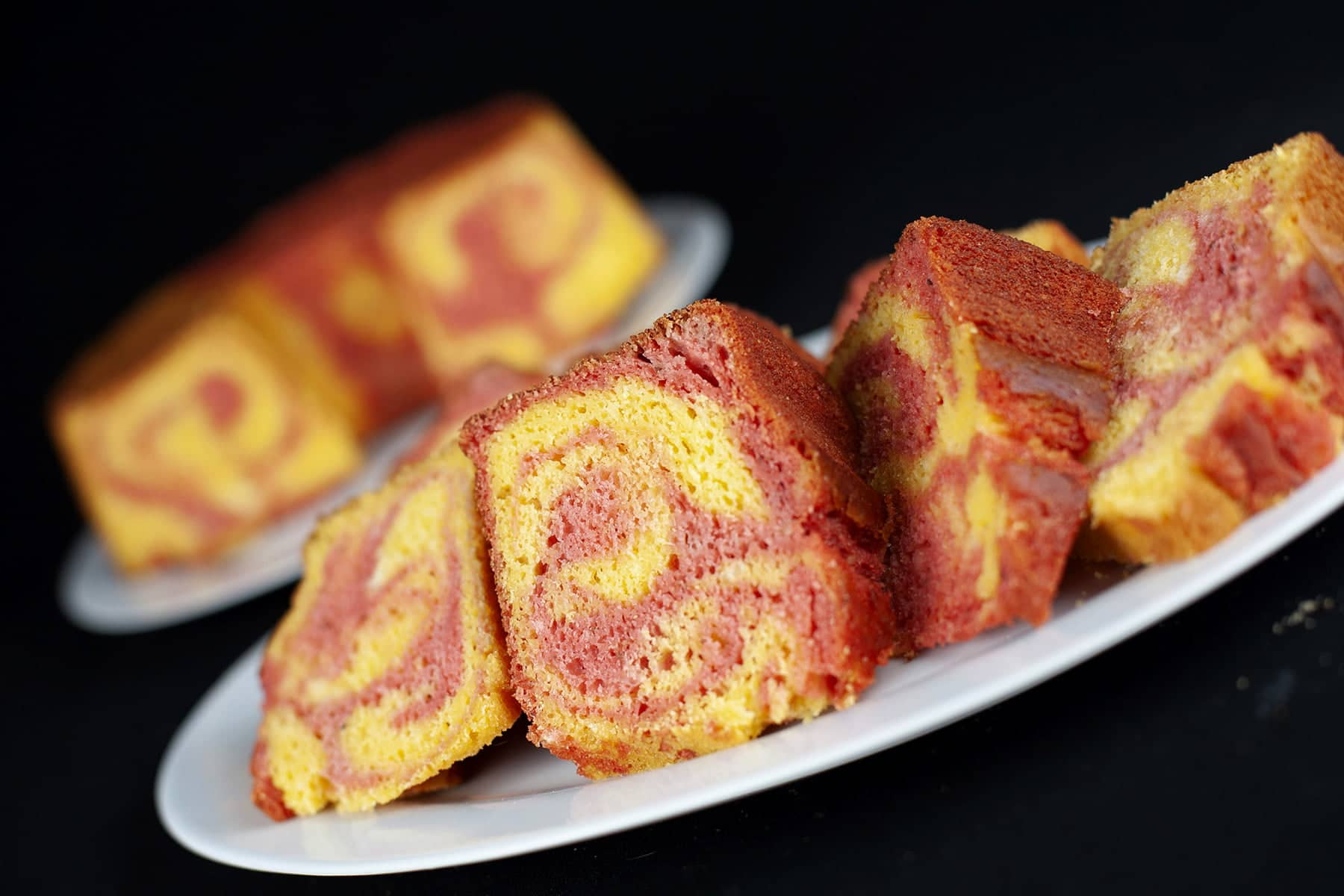A plate of sliced strawberry mango marble cake slices rests in front of the cake it was cut from. The cake is made of brightly coloured pink and orange batters, marbled together,