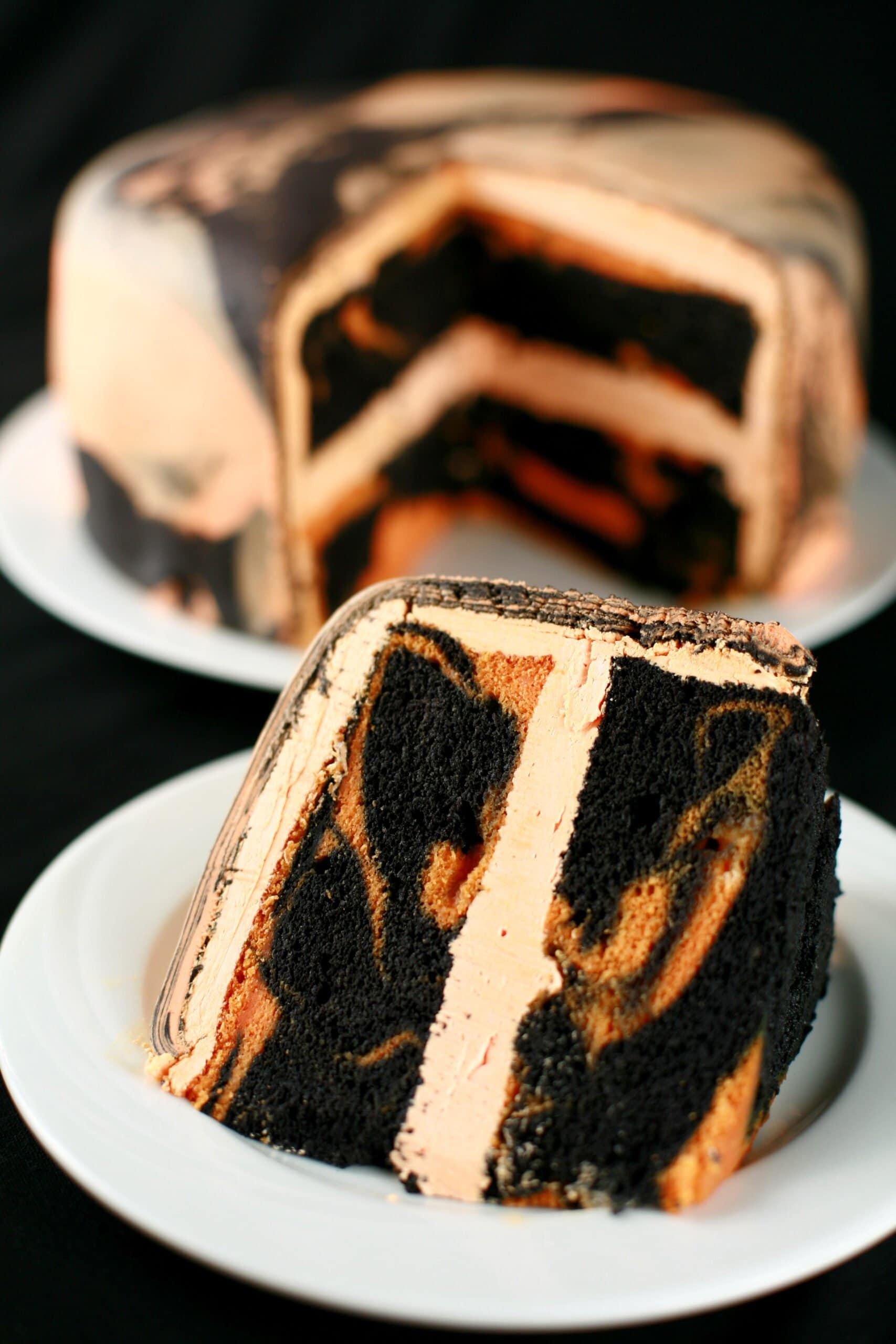 A large round tiger tail cake - black licorice and orange marbled cake, with orange buttercream - is shown with a slcie cut out, and served on a plate in front of it.
