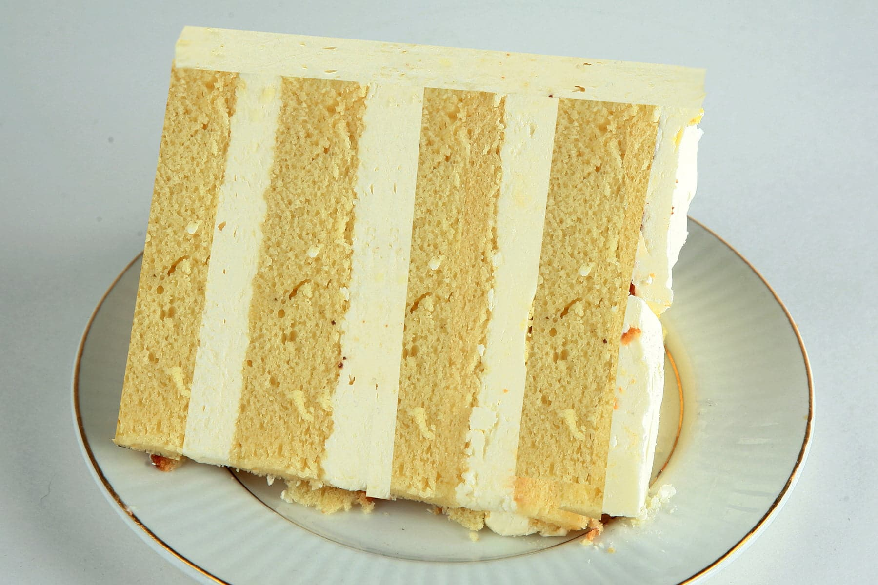 A slice of white chocolate amaretto cake.  4 layers of a yellowish cake, separated by layers of white chocolate buttercream.