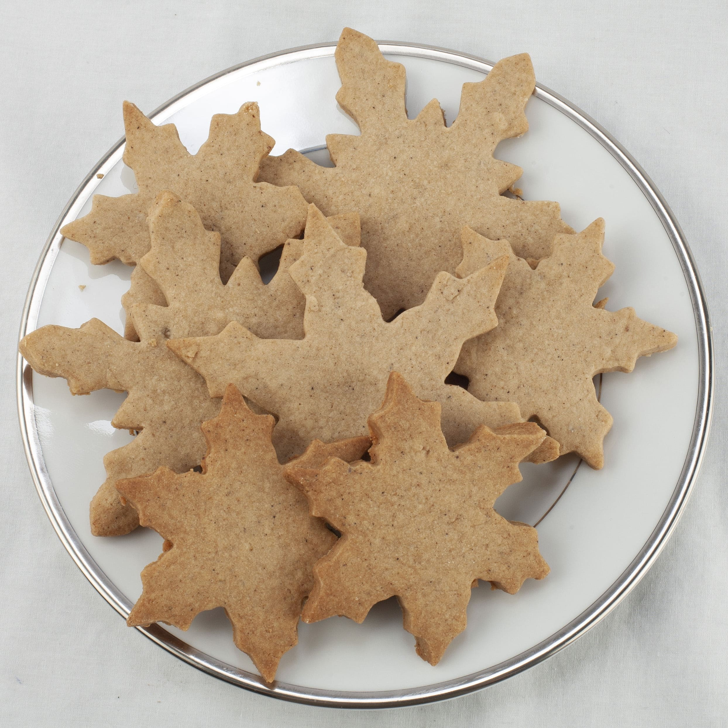 A pile of golden brown chai shortbread cookies - shaped like snowflakes - are piled on a small white plate.