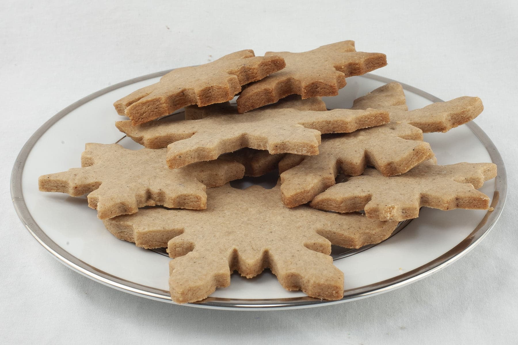 A pile of golden brown shortbread cookies - shaped like snowflakes - are piled on a small white plate.