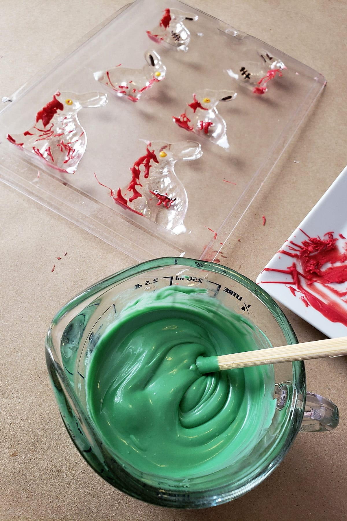 A measuring cup full of green melted candy rests next to a decorated chocolate bunny mold.