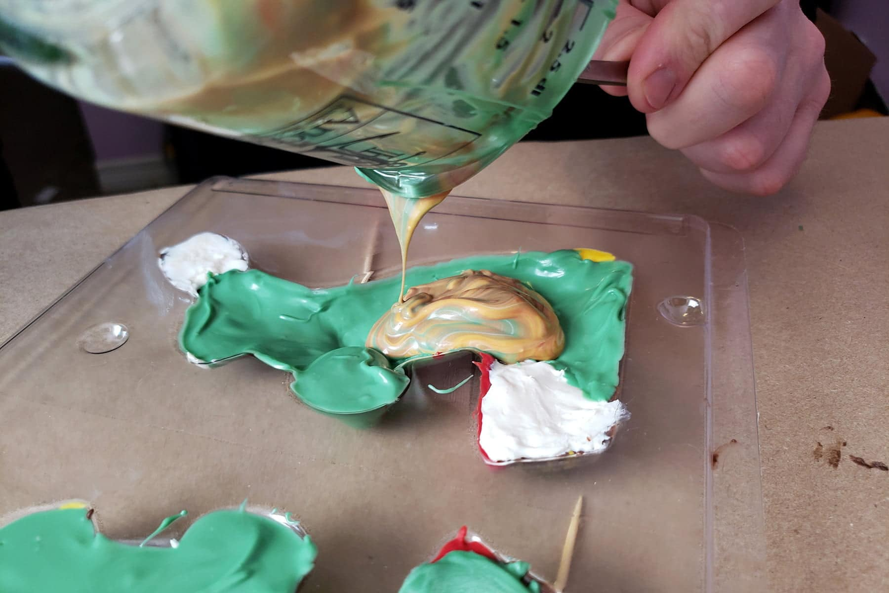 A measuring cup filled with a marbled mix of melted candy is pouring it into a perpared bunny mold.