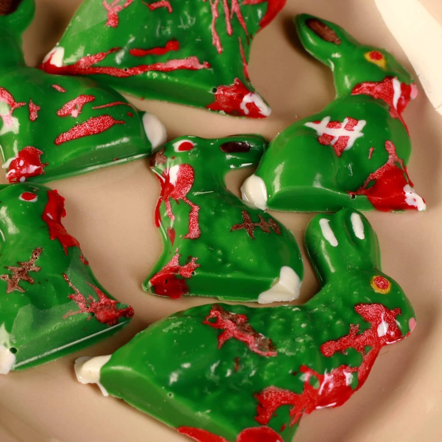 6 different Chocolate Zombie Easter Bunnies are arranged on a beige coloured oval plate. They're all green with red, white, and brown designs to make them look blood spattered, scarred, etc.