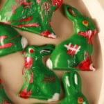 6 different Chocolate Zombie Easter Bunnies are arranged on a beige coloured oval plate. They're all green woth red, white, and brown designs to make them look blood spattered, scarred, etc.