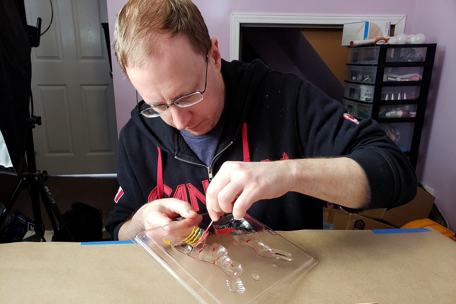 A blond man uses a toothpick to apply melted candy to the details of a clear plastic bunny mold.