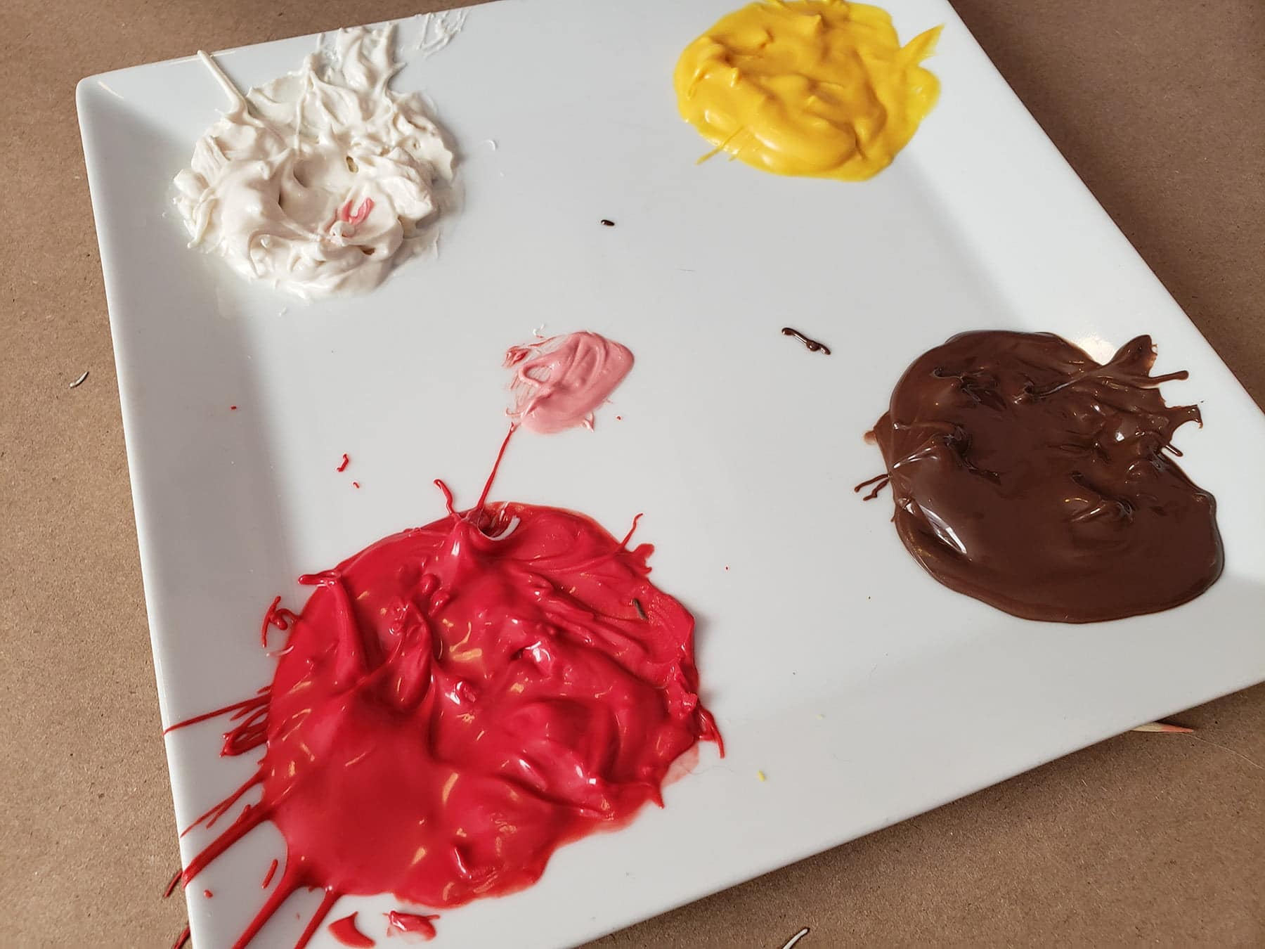 The plate of melted candy shows a bit of red and white having been mixed together to form pink.