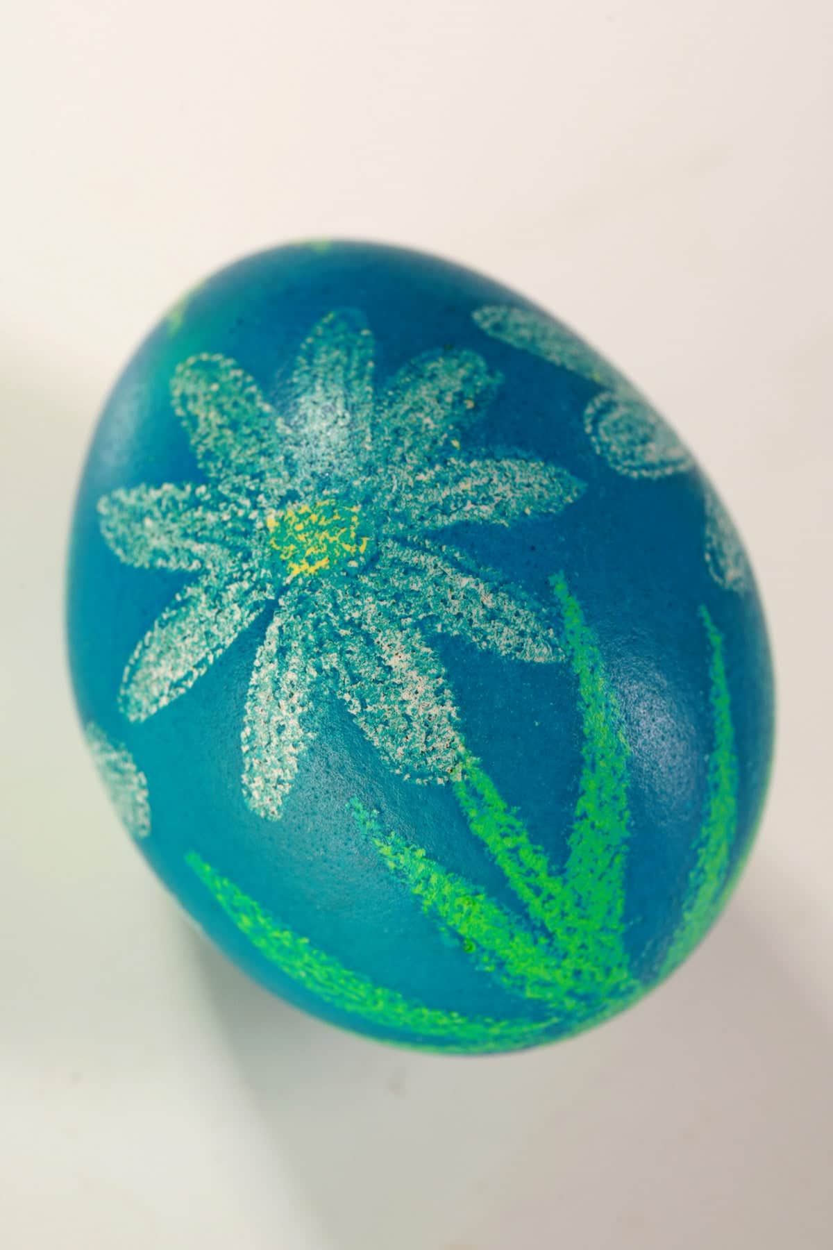 A blue pysanky dyed egg has white daisies with green stems on it.