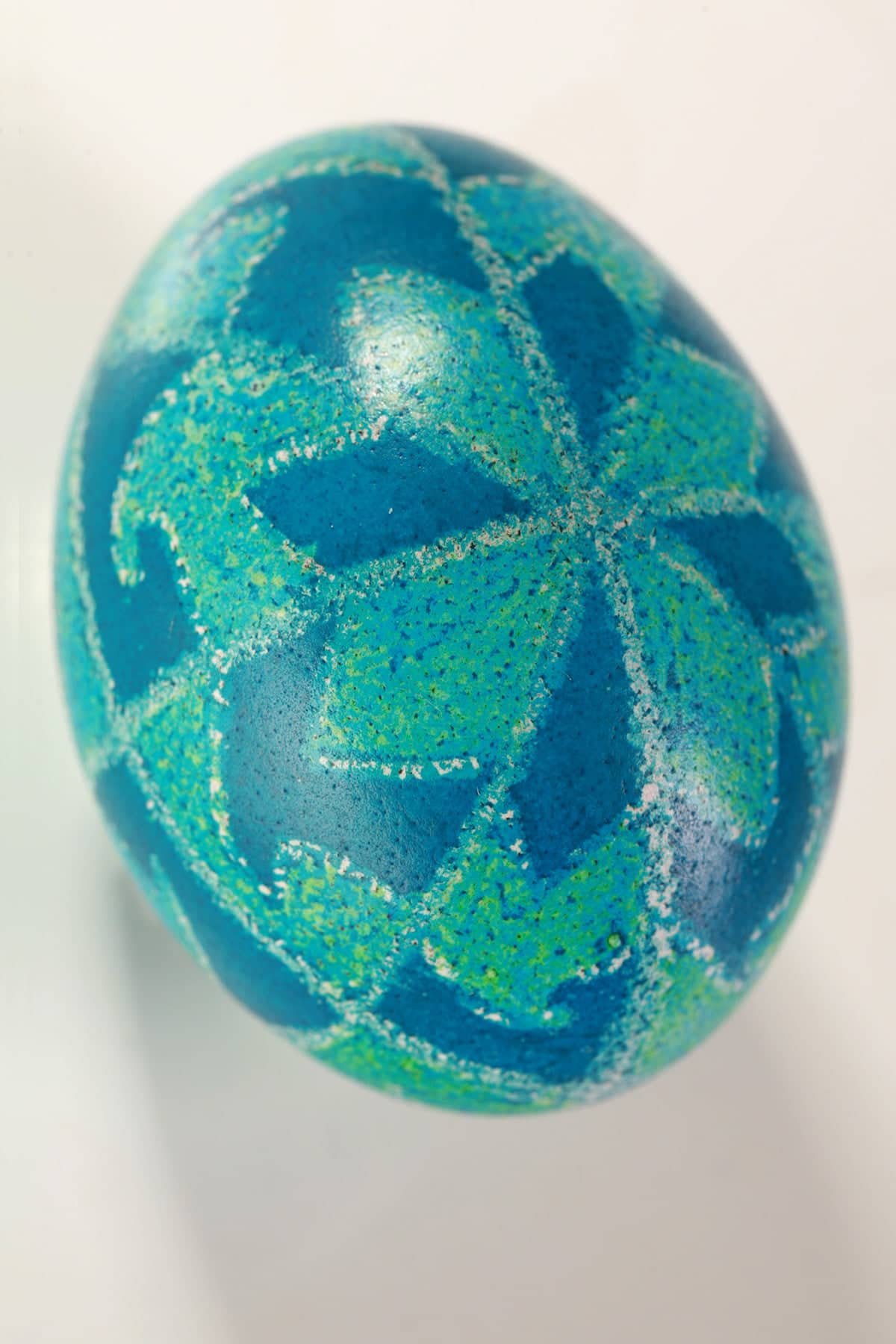 A teal and blue pysanky dyed Easter egg with a geometric design covering it.