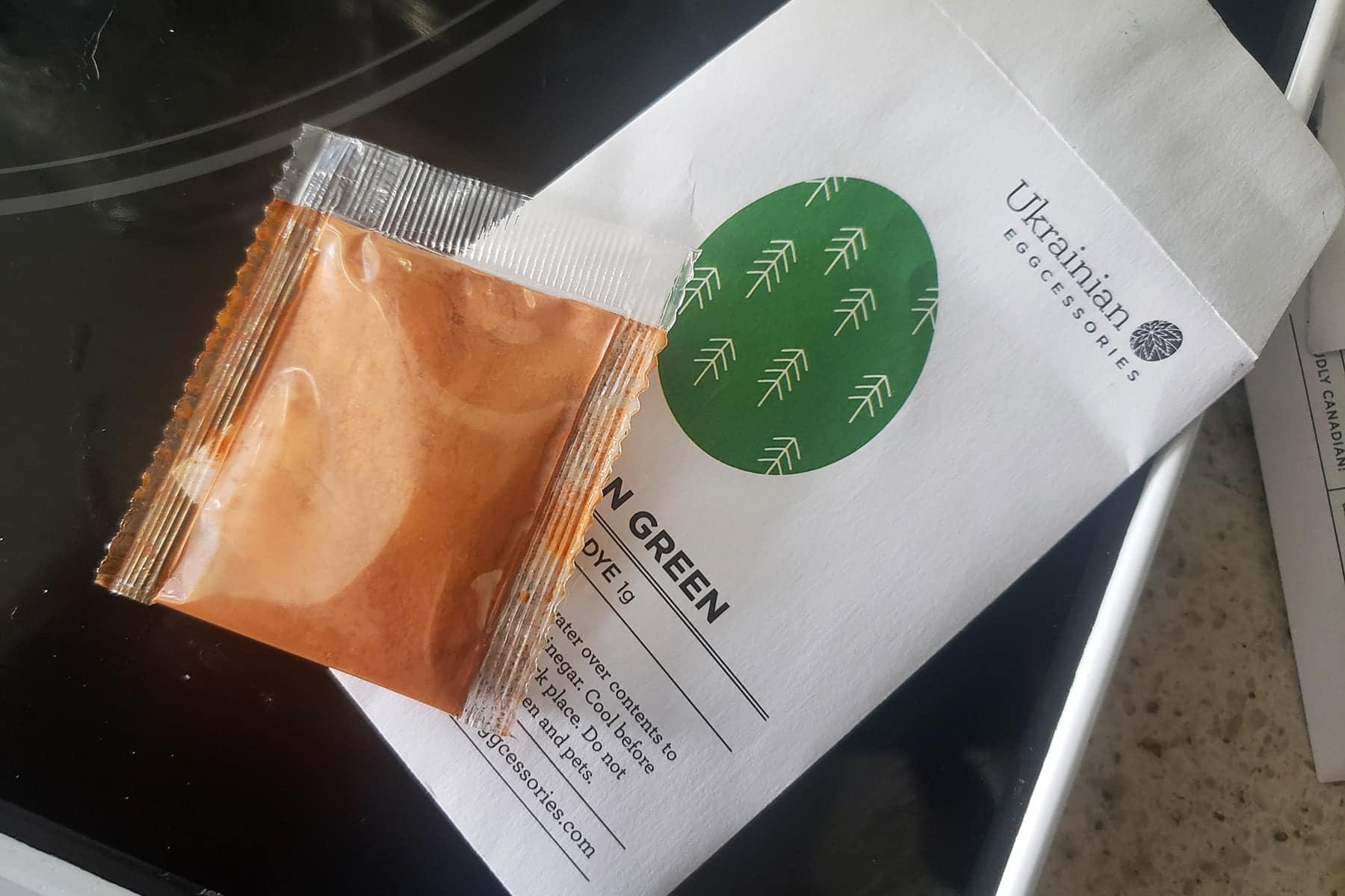 An envelope of green pysanky dye is shown under a little packet of orange powder.