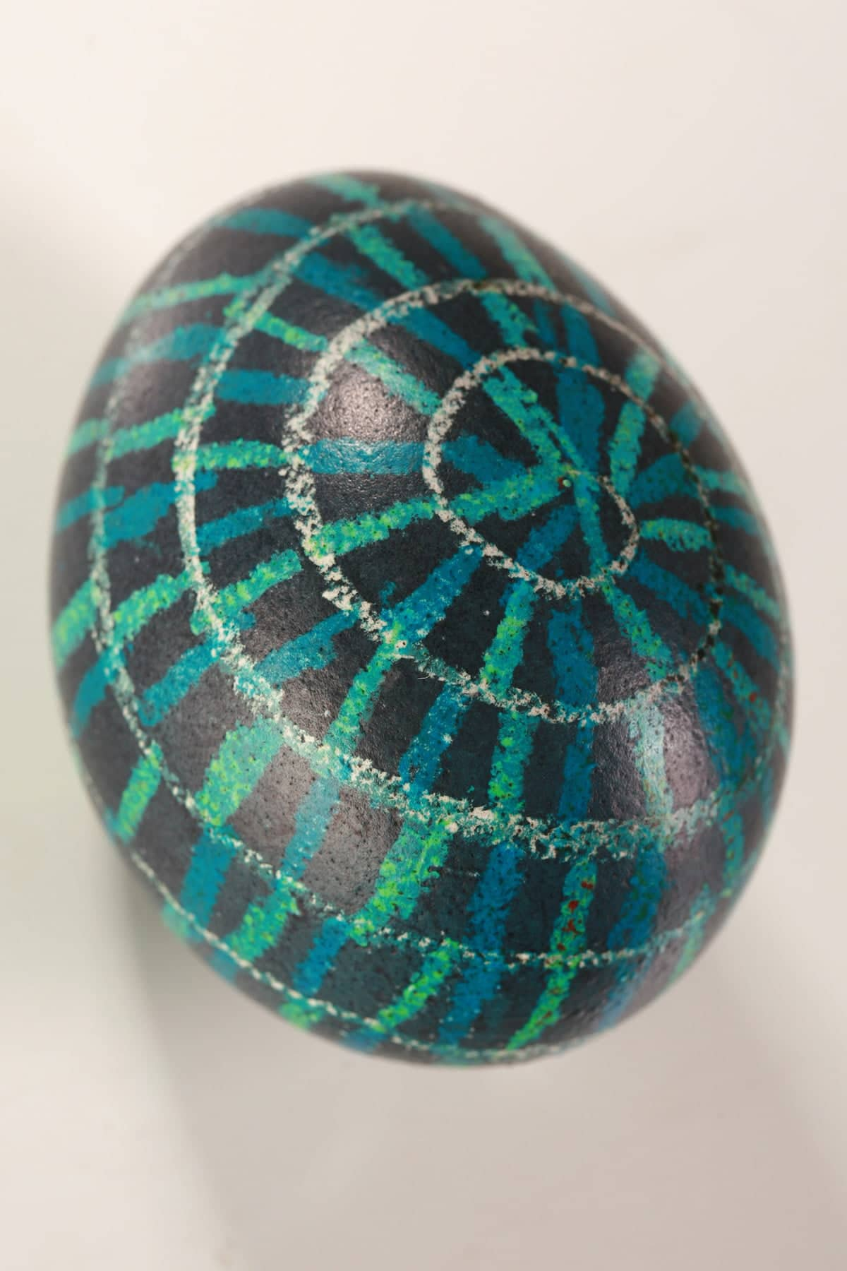 A shiny, dark blue easter egg with a white, blue, and green spiralladder design dyed into it with wax resist technique.