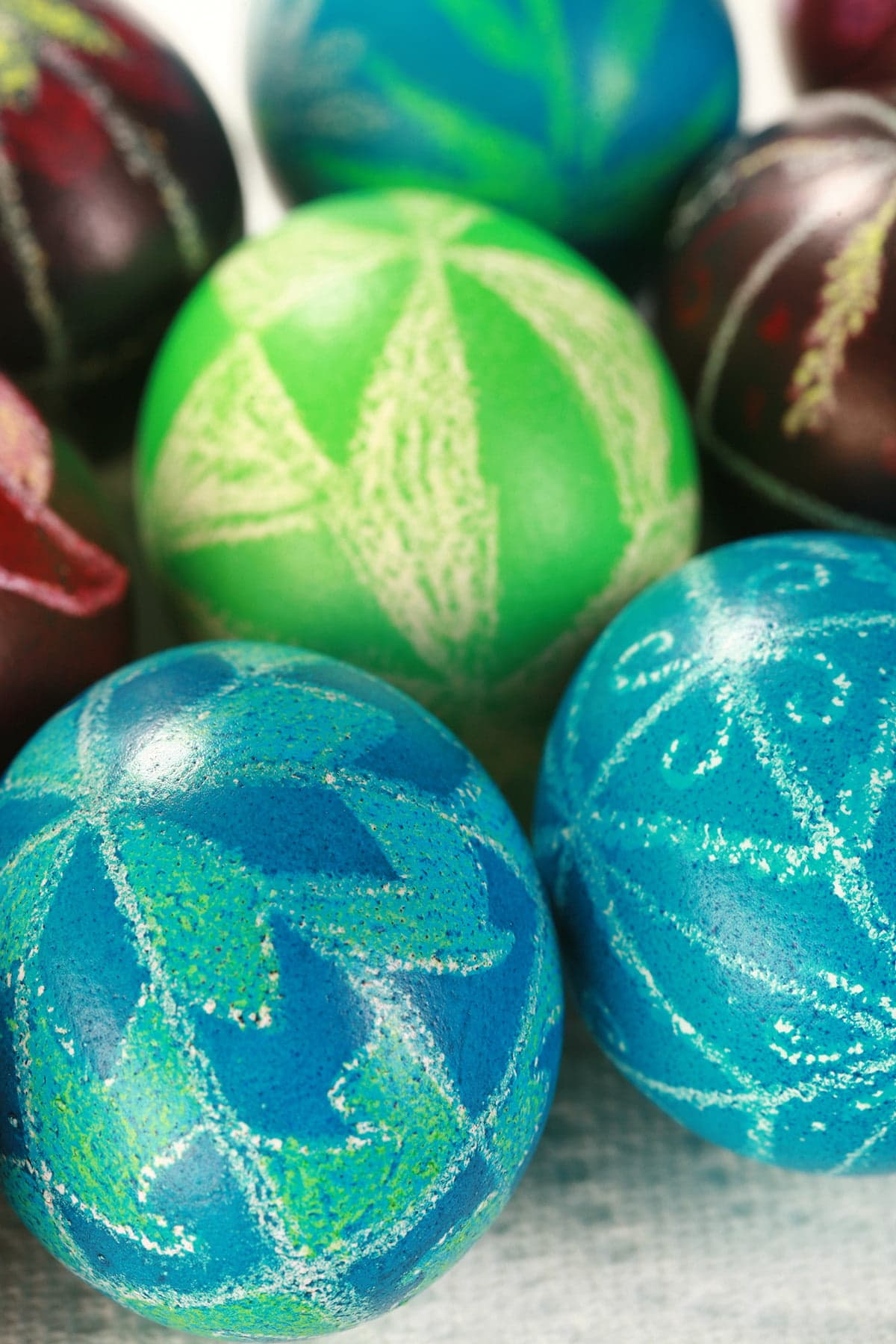A close up view of several brightly coloured pysanky easter eggs.