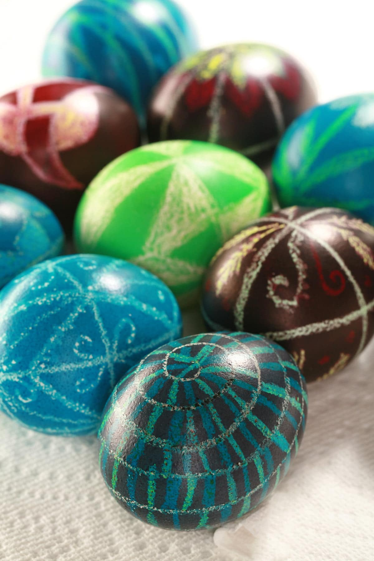 Several brightly coloured batik dyed easy pysanky easter eggs, on a white background.