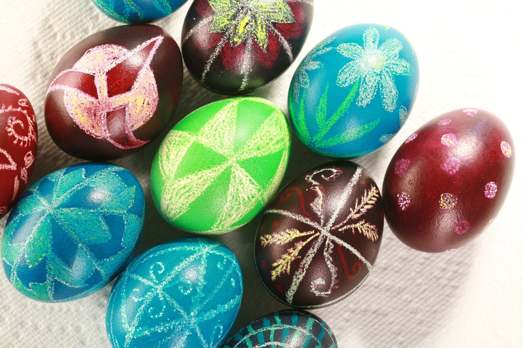 Several brightly coloured wax resist dyed pysanky easter eggs, on a white background.
