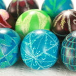 Several brightly coloured wax relief dyed pysanky easter eggs, on a white background.