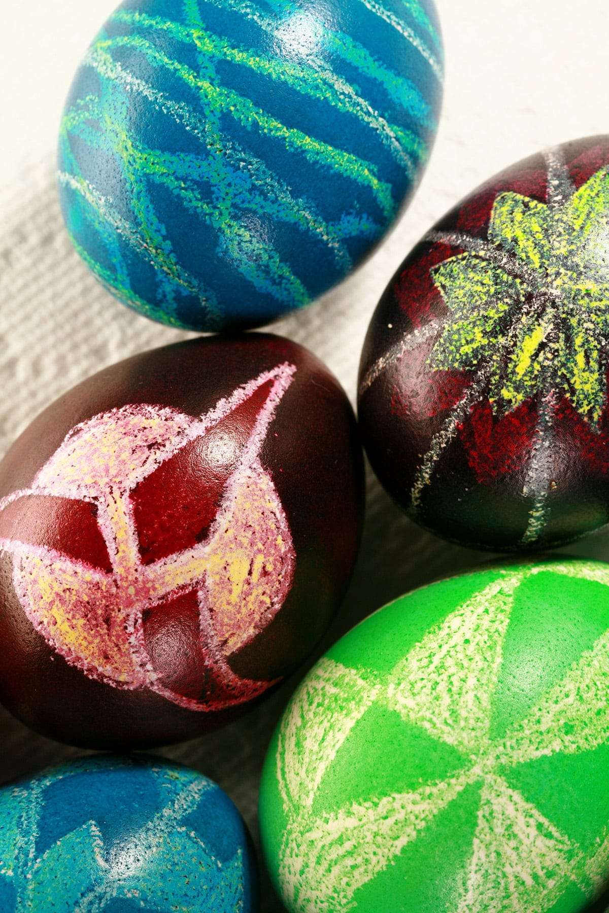 A close up view of several brightly coloured pysanky easter eggs. One has a Klingon symbol on it.