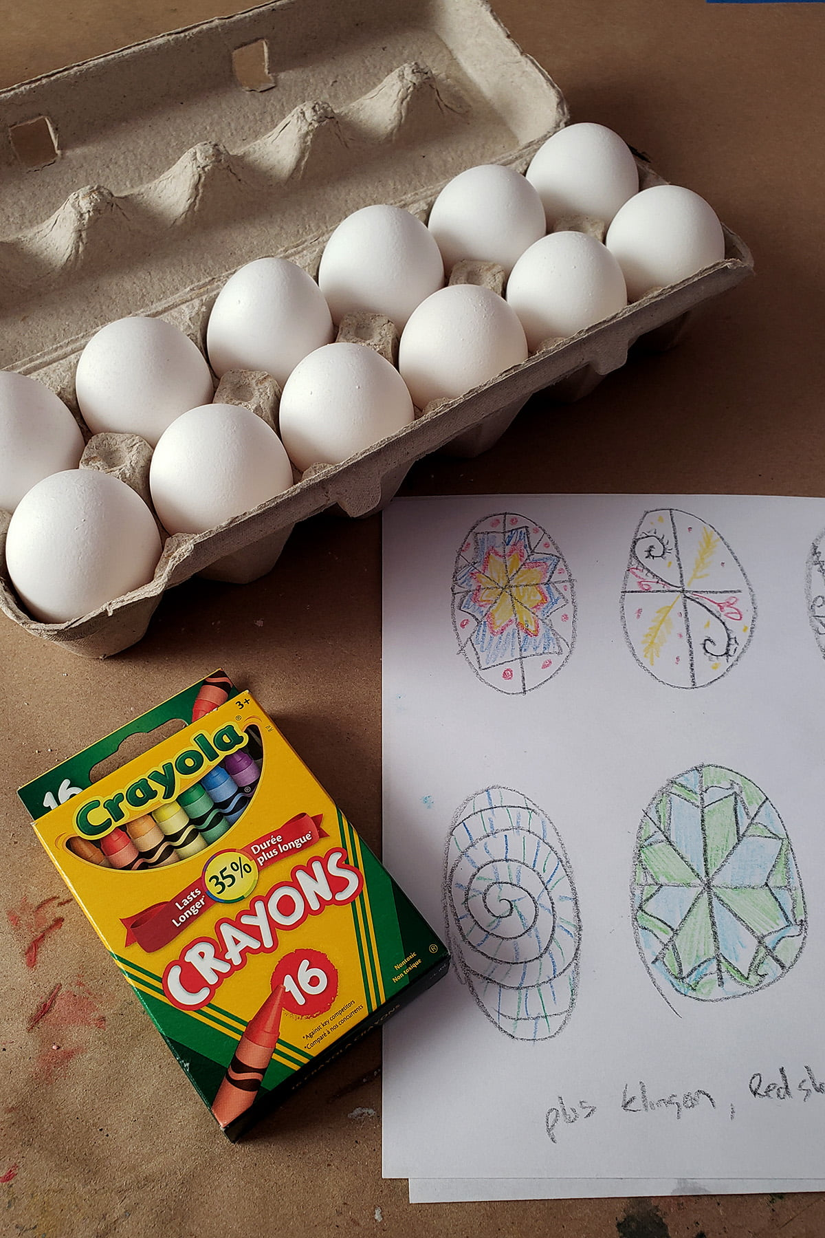 A carton of 12 eggs is shown next to a pack of crayons and a paper with sketches of egg designs on it.