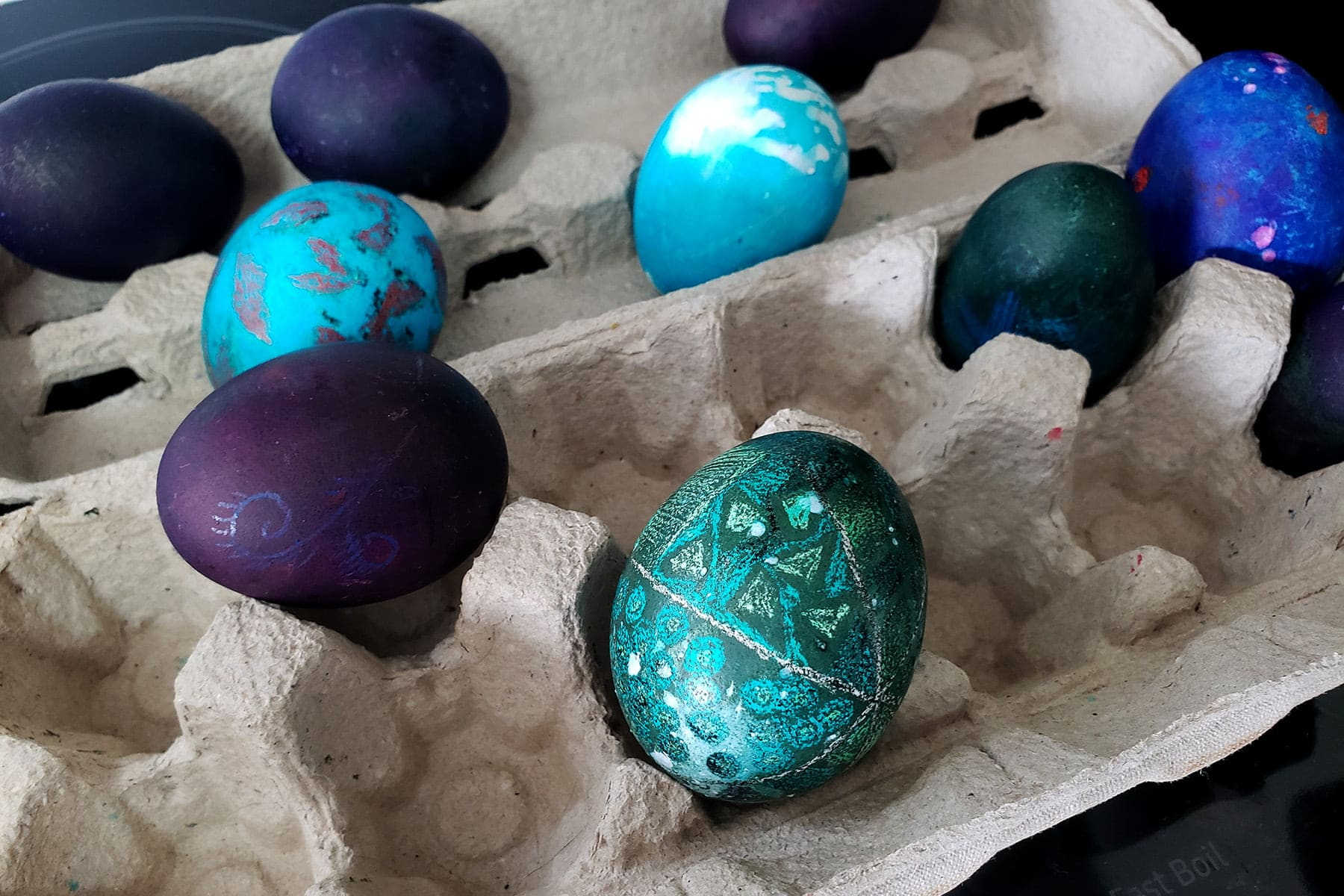 A carton of eggs has several dyed eggs in it. There are blotches of white on them.