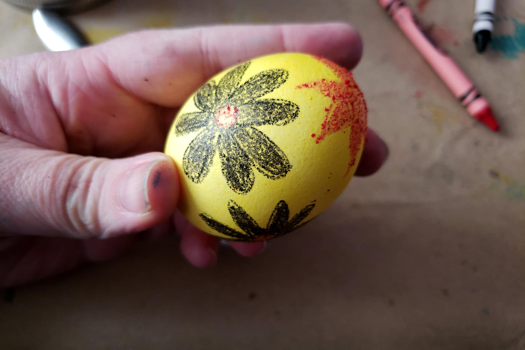 A yellow Easter egg has a black daisy and a red sun drawn onto it in wax.