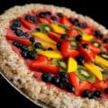 A close up view of a frozen dessert pizza: Rice Crispy Treat crust, dark pink sorbet, and brightly coloured fruit in concentric circles. Kiwi slices, blueberries, strawberry slices, and long slices of mango are all featured.
