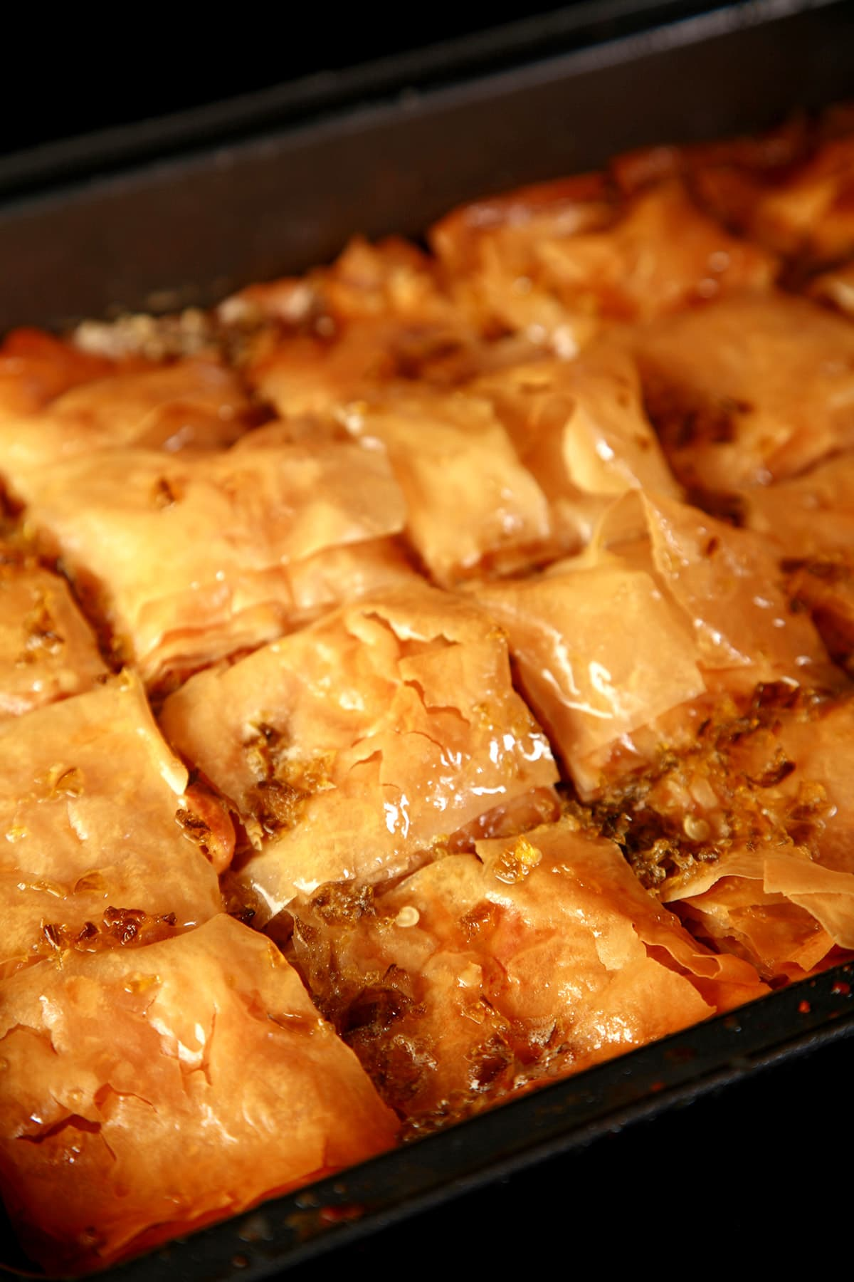 A close up view of a pan of jalapeno beer baklava, cut into squares.