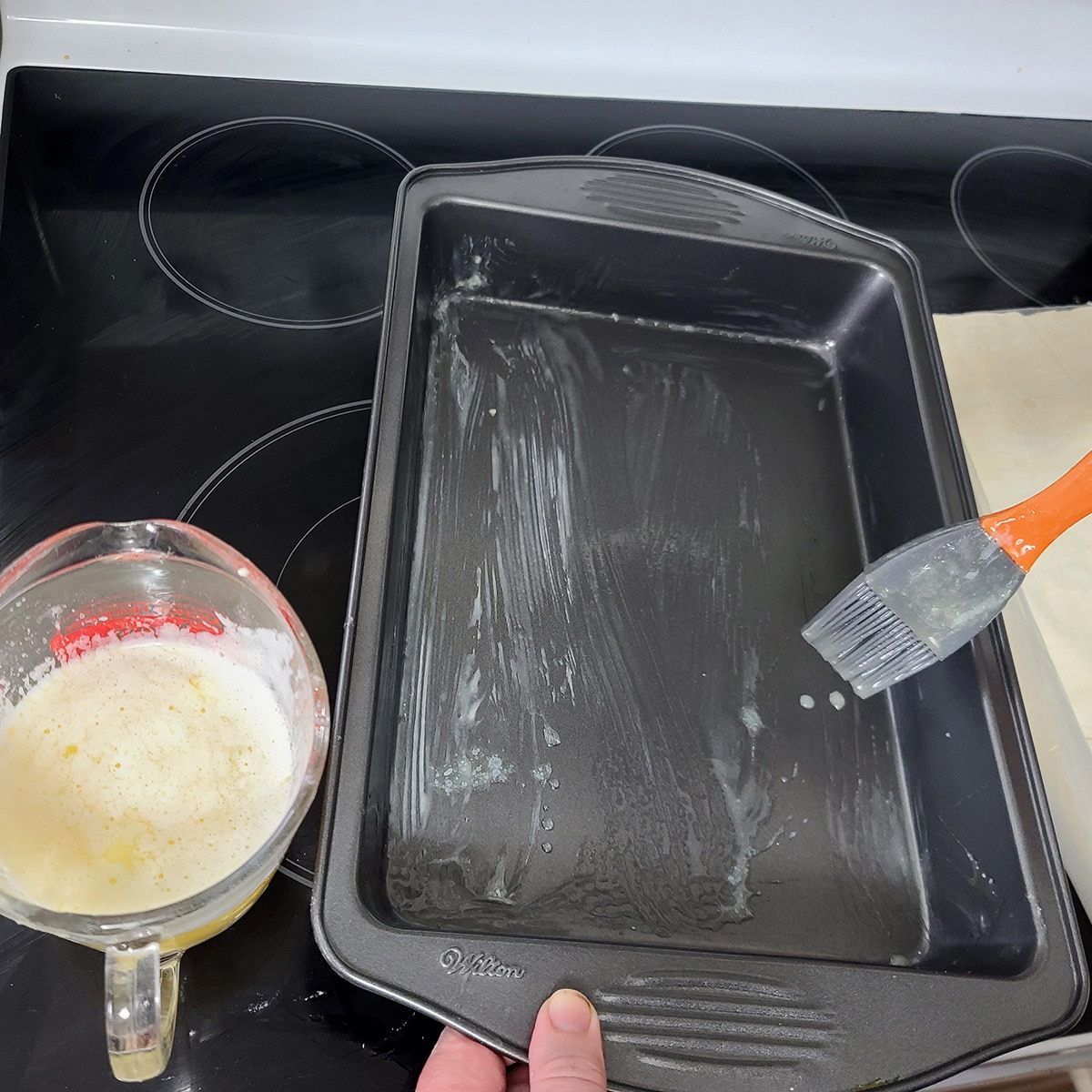 Melted butter is being brushed into a 9 by 13 pan.