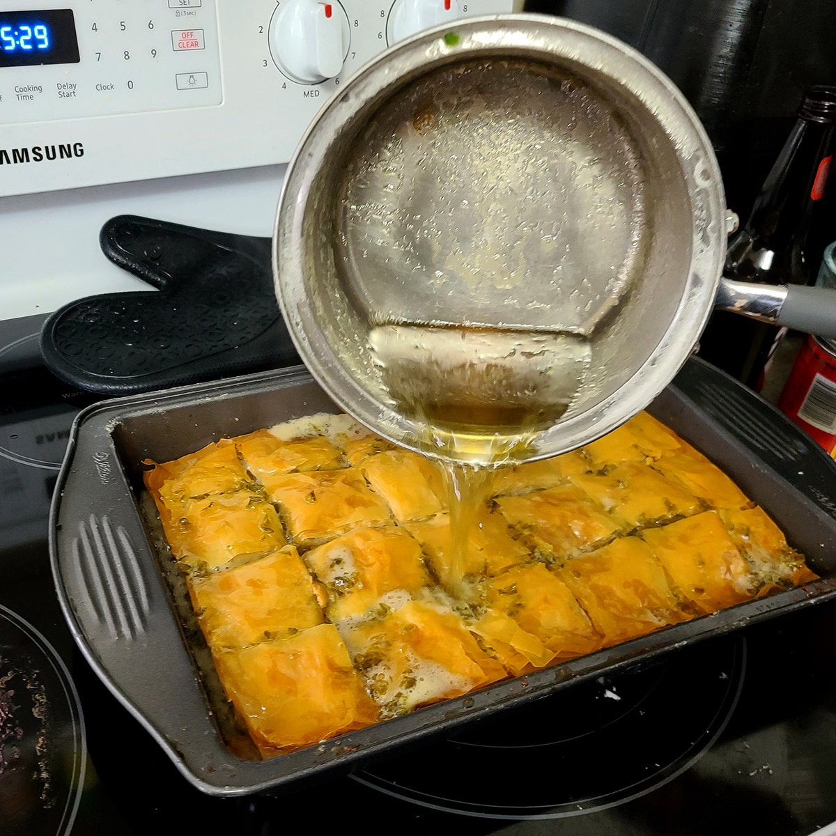 A small pot of honey jalapeno beer mixture being poured over the baked baklava.