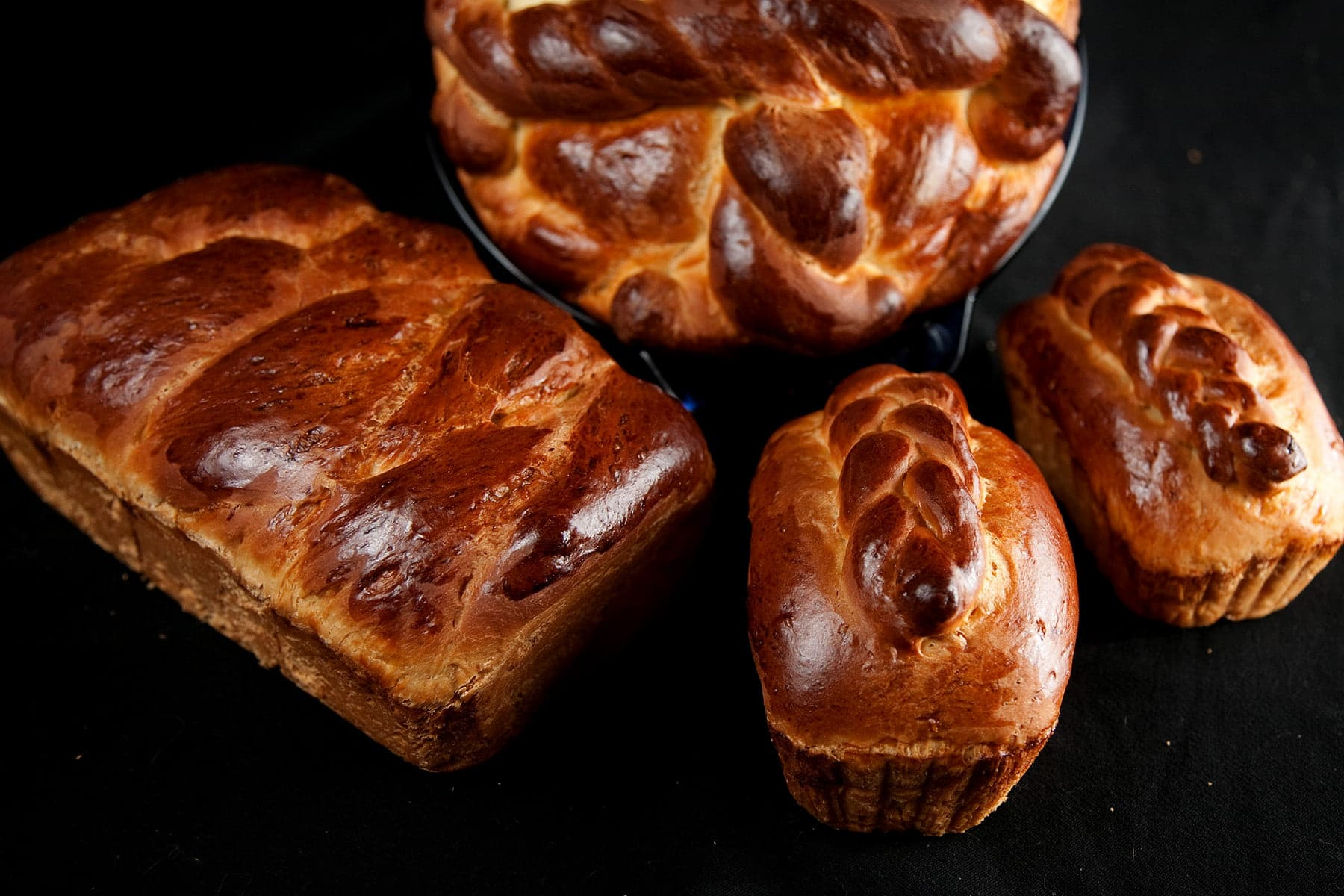 4 loaves of braided and twisted Paska - a Ukrainian Easter bread - on a black background.