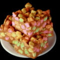 A white plate is stacked with Confetti Bars - rainbow marshmallows held together with butterscotch fudge.