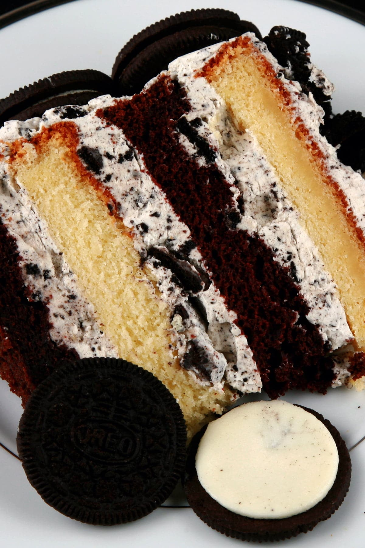 A slice of Cookies N'Cream Cake: A layered chocolate and vanille torte, filled with vanilla Buttercream and Oreo cookies. The cake slice is on a white place, against a black background.