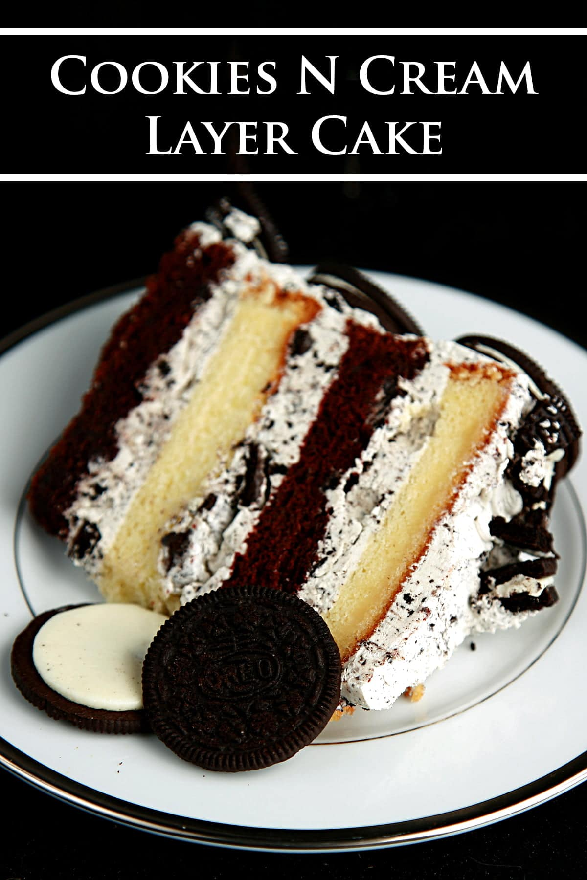 A slice of Cookies N'Cream Cake: A layered chocolate and vanilla torte, filled with vanilla Buttercream and Oreo cookies. The cake slice is on a white place, against a black background.
