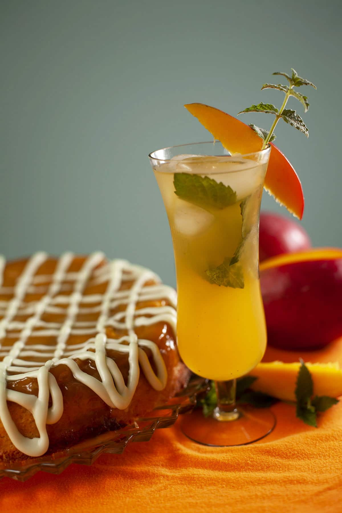 A mango mojito upside down cake: a large round single layer mango upside down cake, on a glass plate.  It has a white icing drizzled over it, and has a sprig of fresh mint on the side of the plate.  There is a tall tulip glass with a mango mojito next to the cake.