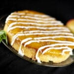 A mango mojito upside down cake: a large round single layer mango upside down cake, on a glass plate. It has a white icing drizzled over it, and has a sprig of fresh mint on the side of the plate.
