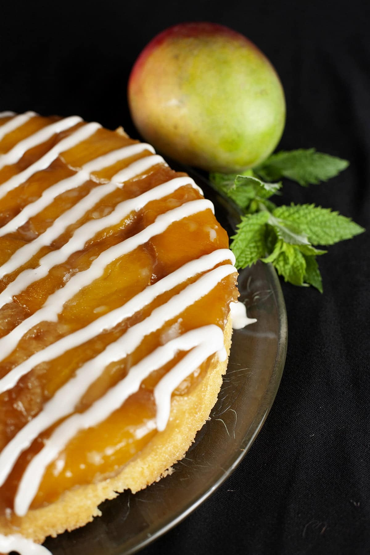 A mango mojito upside-down cake: a large round single layer mango upside-down cake, on a glass plate. It has a white icing drizzled over it, and has a sprig of fresh mint on the side of the plate.