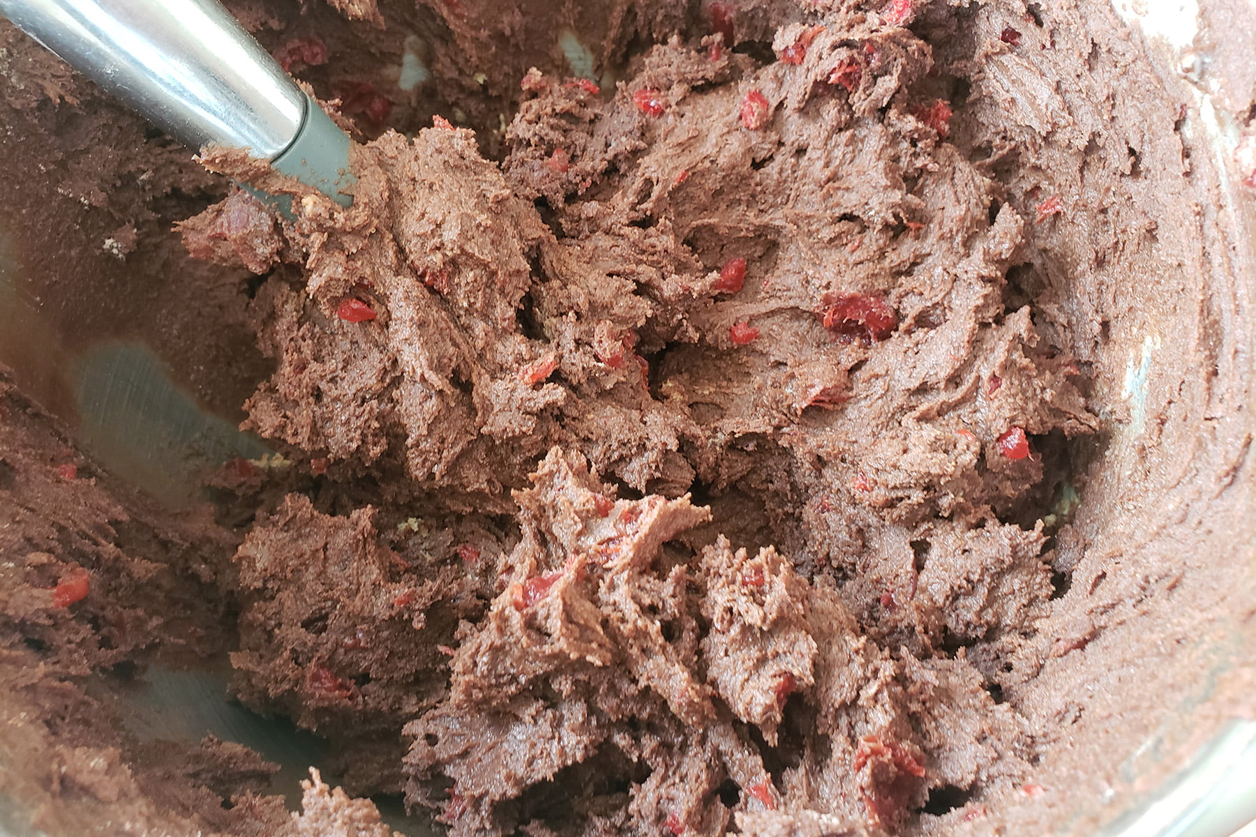 A close up view of a mixing bowl with chocolate cookie dough in it. The dough is generously studded with bits of maraschino cherries.