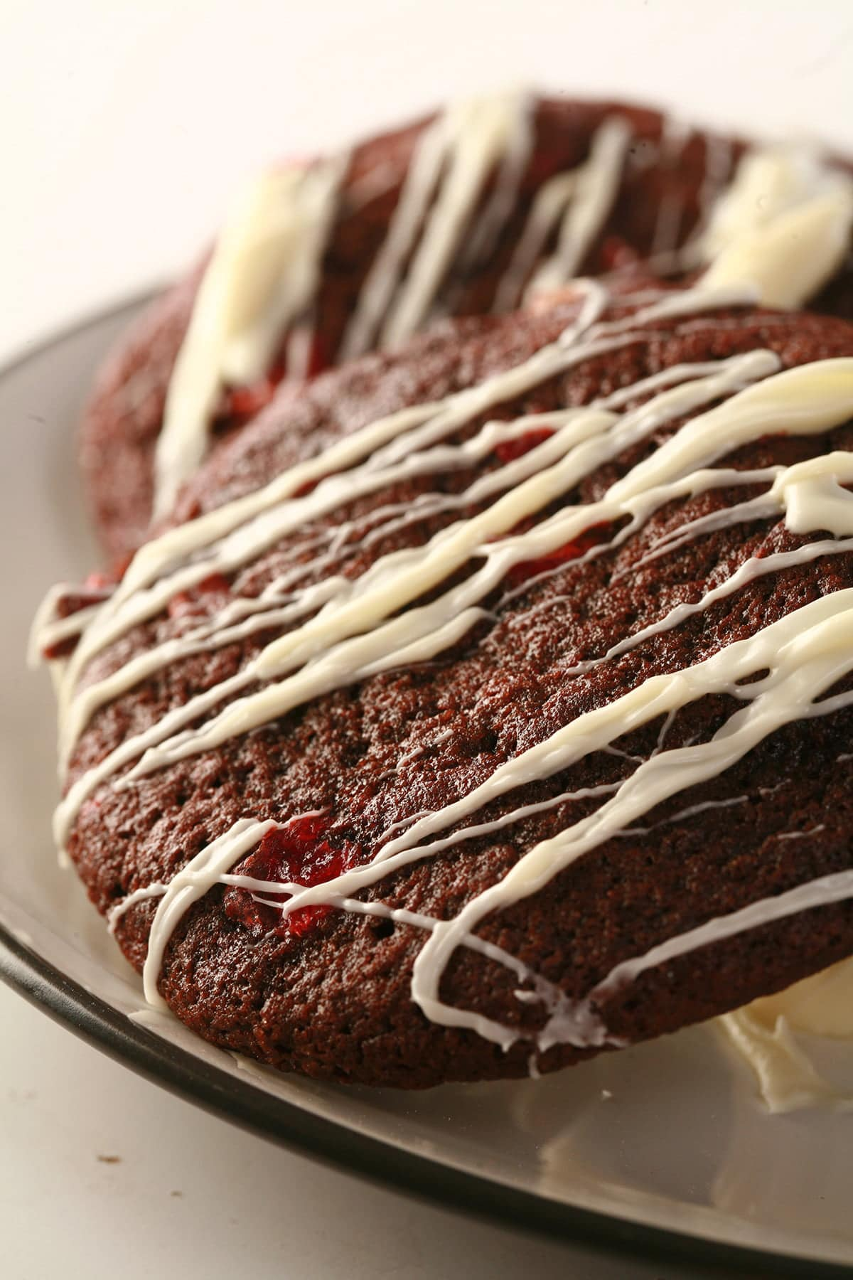 A plate of chewy chocolate black forest cookies, studded with bits of maraschino cherry and drizzled in white chocolate.