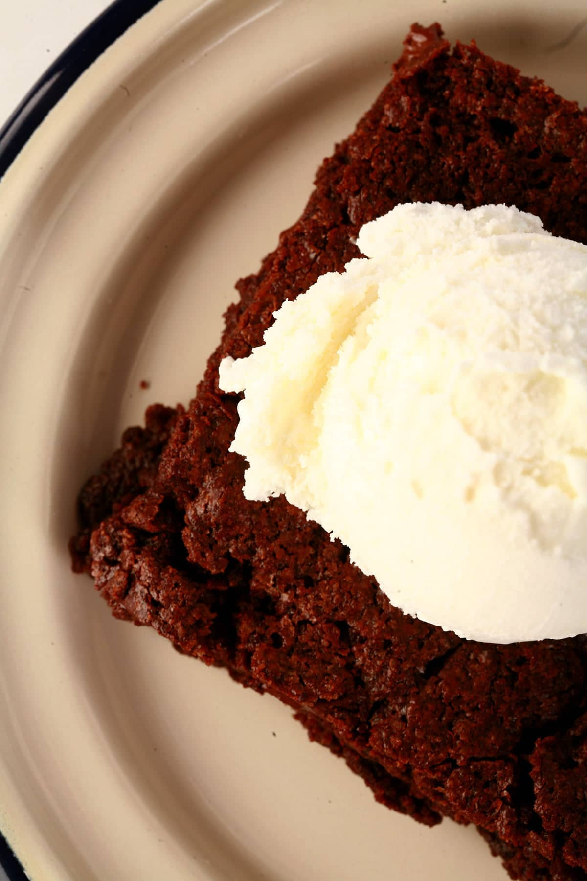 A large double chocolate brownie, topped with vanilla ice cream.