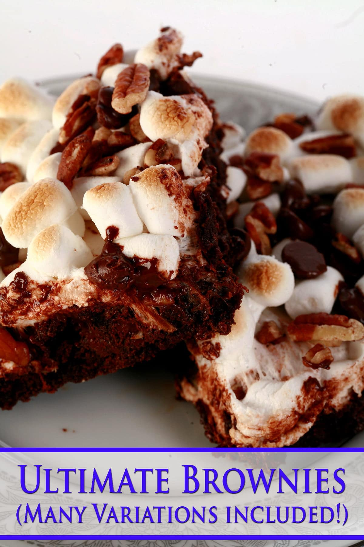 A close up view of two rocky road brownies - double chocolate walnut brownies with toasted mini marshmallows, chocolate chips, and chopped pecans on top.
