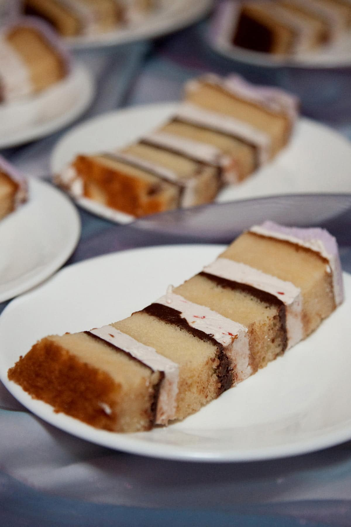 Slices of layered raspberry tiramisu torte are on small plates, laid out on a table.