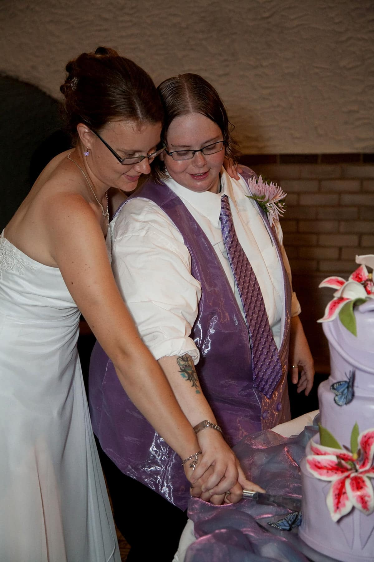 Two women - one in a wedding dress, one in a suit with a purple vest and tie - cut their wedding cake.