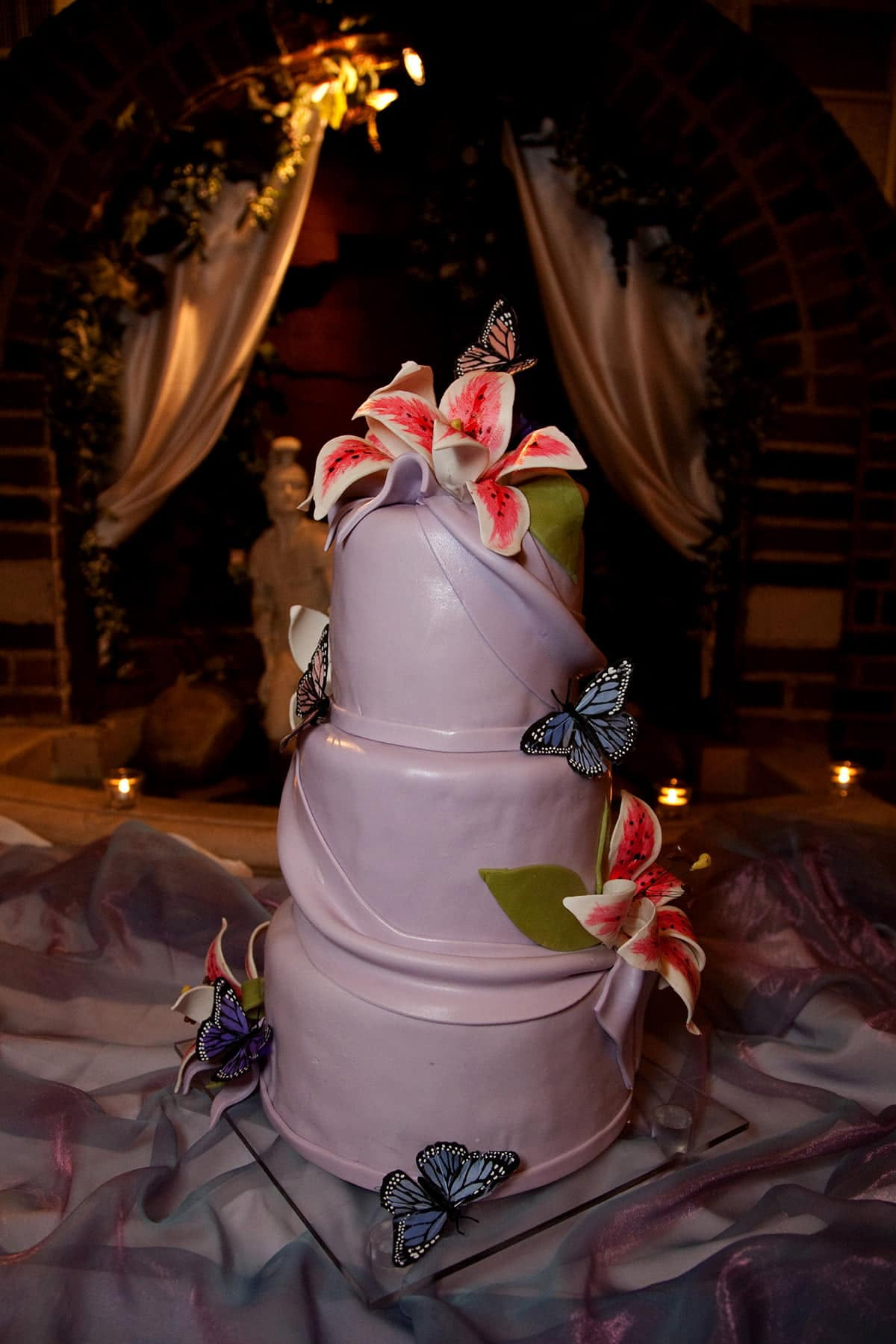 A 3 tiered purple wedding cake. The cake is covered in lavender fondant, and features swags of matching fondant and sugar Stargazer Lilies.