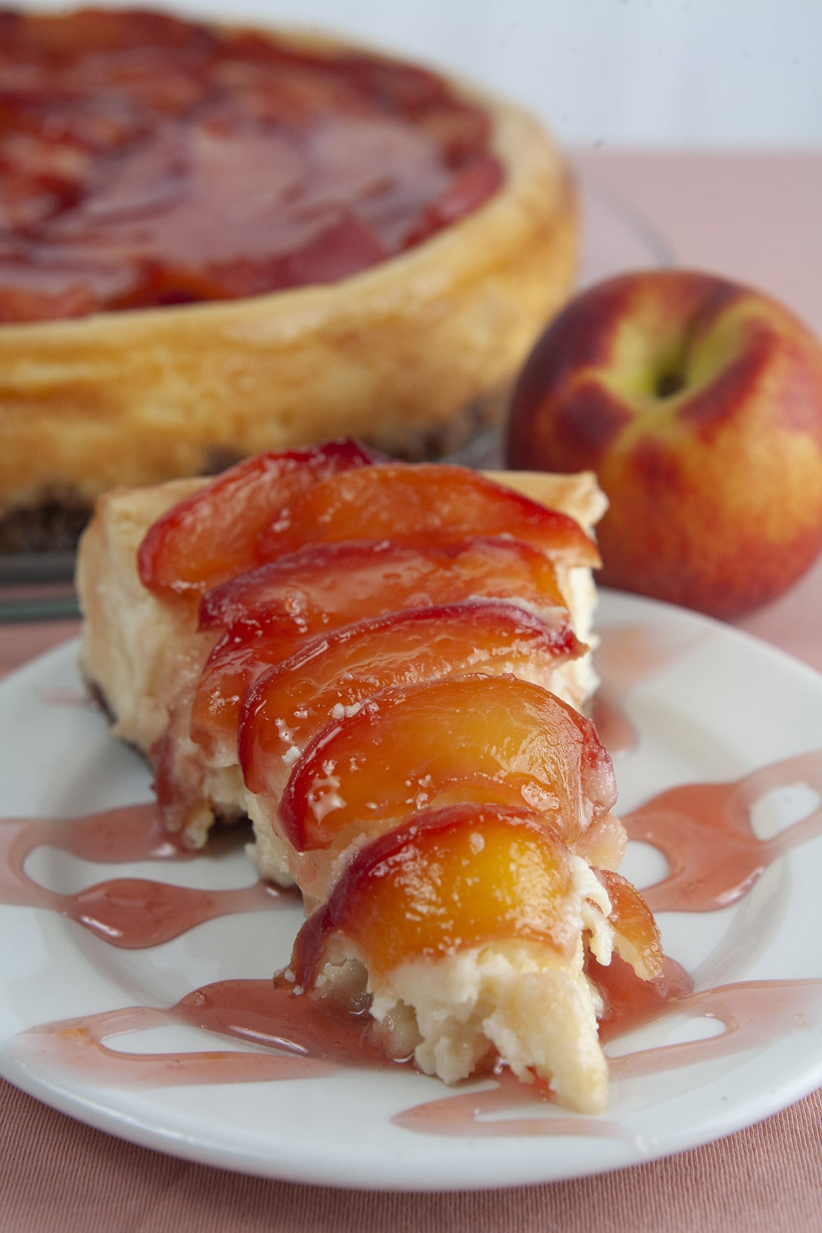 A slice of peach cheesecake with a pink drizzle, next to the whole cheesecake, and a fresh peach.