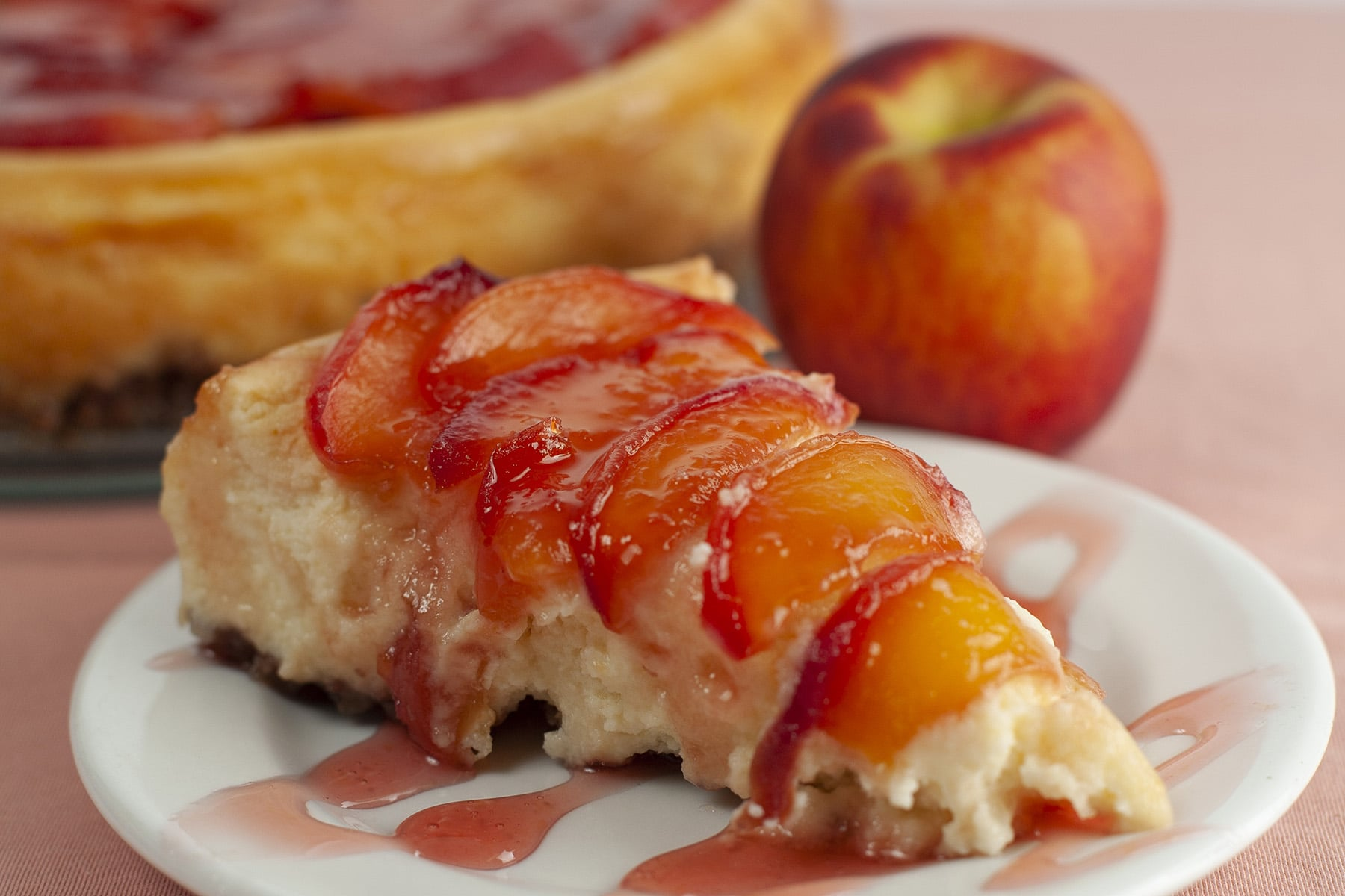 A slice of peachy southern comfort cheesecake, in front of the whole cheeseacake and a fresh peach.