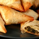 A small blue plate is piled with flaky Spanakopita Triangles. One is cut in half to show the spinach filling.