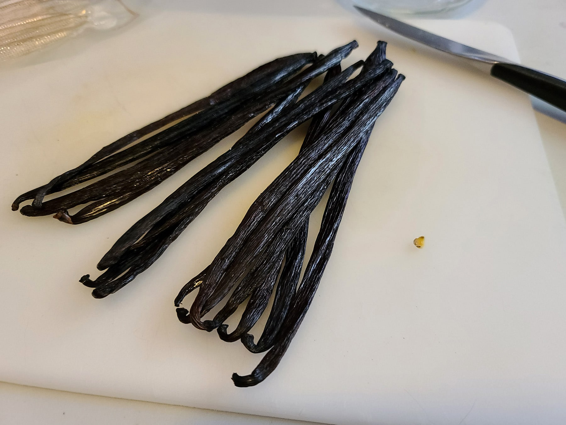A pile of vanilla beans on a cutting board.
