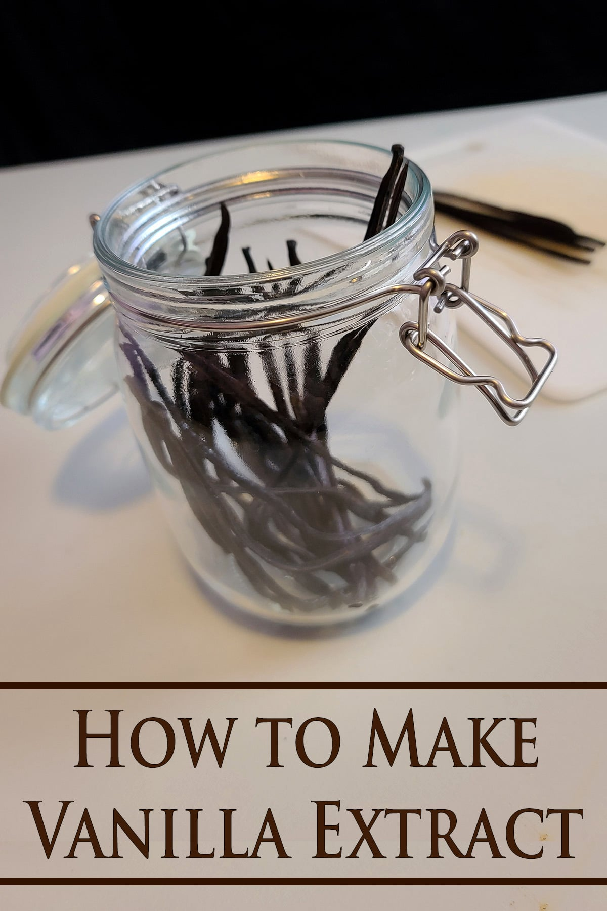 A glass jar with several split vanilla beans in it. Brown text overlay says how to make vanilla extract.